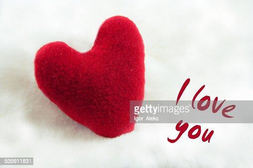 Handmade plush red heart on the soft white blanket. : Stock Photo