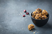 Food and drink, healthy lifestyle, eating, diet and nutrition, snack, superfood concept. Handmade raw vegan protein energy balls with sesame seeds, dry cranberry, nuts, honey. Copy space background