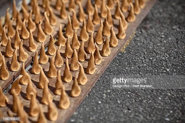 handmade sandalwood incense dries in the sun on the street side