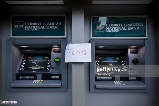 A handmade sign that reads End sits taped between automated teller machines outside a National Bank of Greece SA bank branch in Thessaloniki Greece...