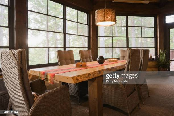 Handmade wooden dining table with high-back wicker chairs