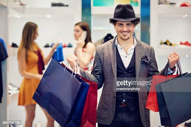 Handosme Mann ist Possing mit seinem Einkaufstüten in einer boutique