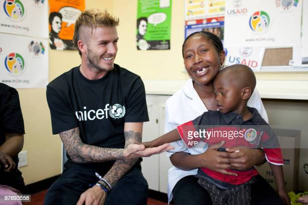 Handout photo made available by UNICEF shows British footballer David Beckham playing with threeyearold Sesiphi whose mother Tamara is HIV positive...