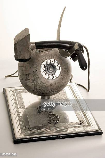 A handout photo shows a telephone set made as a terrestrial globe with Soviet hammer and a sickle symbols as a handset on it during an exhibition...
