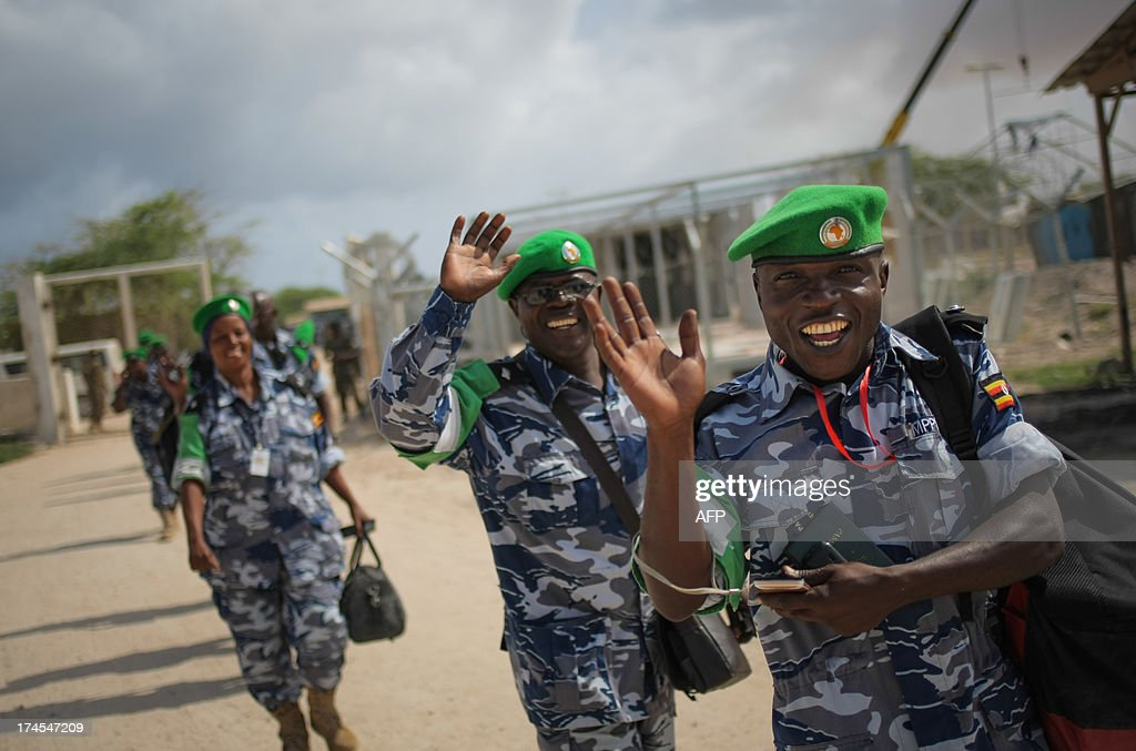 A handout photograph taken and released by the African Union-United Nations Information Support Team on July 27, 2013, shows Ugandan police officers waving as they prepare to board a United Nations aircraft at Aden Abdulle International Airport in Mogadishu, after having completed their one-year tour serving as formed police units with the African Union Mission in Somalia (AMISOM). The outgoing 135 police officers were replaced by a unit of the same number that arrived from Uganda today to begin their own 12-month long deployment serving with the AU mission in the Horn of Africa nation. AFP PHOTO / AU-UN IST PHOTO / STUART PRICERESTRICTED TO EDITORIAL USE - MANDATORY CREDIT 'AFP PHOTO / AU-UN IST / STUART PRICE' - NO