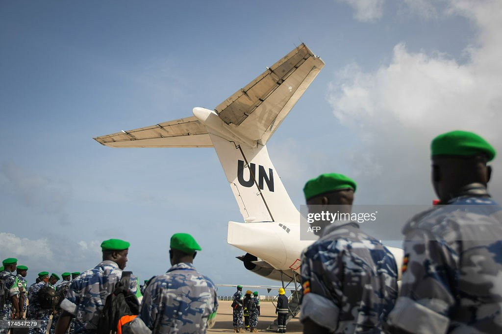 A handout photograph taken and released by the African Union-United Nations Information Support Team on July 27, 2013, shows Ugandan police officers preparing to board a United Nations aircraft at Aden Abdulle International Airport in Mogadishu, after having completed their one-year tour serving as formed police units with the African Union Mission in Somalia (AMISOM). The outgoing 135 police officers were replaced by a unit of the same number that arrived from Uganda today to begin their own 12-month long deployment serving with the AU mission in the Horn of Africa nation. AFP PHOTO / AU-UN IST PHOTO / STUART PRICE CLIENTS