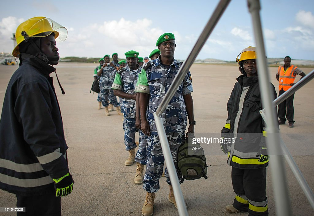 A handout photograph taken and released by the African Union-United Nations Information Support Team on July 27, 2013, shows Ugandan police officers preparing to board a United Nations aircraft at Aden Abdulle International Airport in Mogadishu, after having completed their one-year tour serving as formed police units with the African Union Mission in Somalia (AMISOM). The outgoing 135 police officers were replaced by a unit of the same number that arrived from Uganda today to begin their own 12-month long deployment serving with the AU mission in the Horn of Africa nation. AFP PHOTO / AU-UN IST PHOTO / STUART PRICE CREDIT 'AFP PHOTO / AU-UN IST / STUART PRICE' - NO
