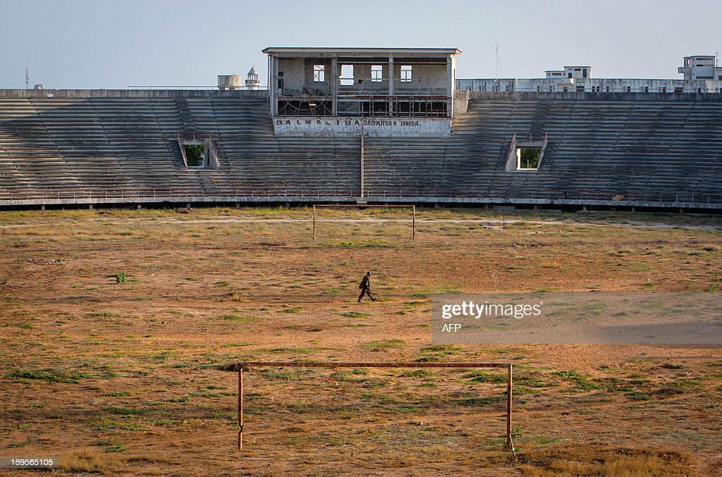 A handout photograph taken on January 12, 2013 and released on January 16 by the African Union-United Nations Information Support Team, shows a Ugandan soldier serving with the African Union Mission in Somalia (AMISOM) walking across the former football pitch inside Mogadishu National Stadium. Formerly a main base for the Al-Qaeda-allied violent extremist group Al Shabaab, the once impressive stadium was used as a headquarters for the group's operations in Mogadishu, a training ground for their fighters and a site where they executed prisoners and tested and assembled improvised explosive devices (IEDs). After two decades of near-constant conflict, Somalia is enjoying its longest period of peace and growing security since the Al-Qaeda-allied violent extremist group Al Shabaab was driven from Mogadishu in August 2011. Under the Shabaab's draconian rule, social pastimes and sports such as football were banned but residents of the city and elsewhere across Somalia.