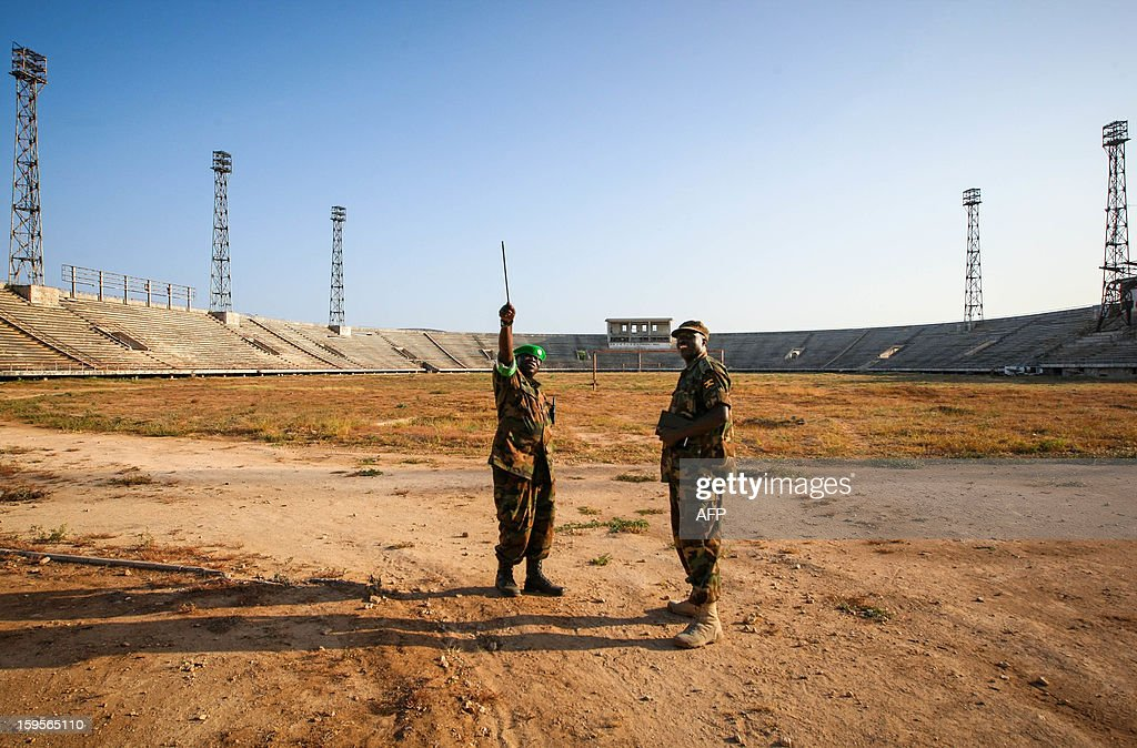 A handout photograph taken on January 12, 2013 and released on January 16 by the African Union-United Nations Information Support Team, shows two Ugandan soldiers serving with the African Union Mission in Somalia (AMISOM) walking across the former football pitch inside Mogadishu National Stadium. Formerly a main base for the Al-Qaeda-allied violent extremist group Al Shabaab, the once impressive stadium was used as a headquarters for the group's operations in Mogadishu, a training ground for their fighters and a site where they executed prisoners and tested and assembled improvised explosive devices (IEDs). After two decades of near-constant conflict, Somalia is enjoying its longest period of peace and growing security since the Al-Qaeda-allied violent extremist group Al Shabaab was driven from Mogadishu in August 2011. Under the Shabaab's draconian rule, social pastimes and sports such as football were banned but residents of the city and elsewhere across Somalia. AFP PHOTO / AU-UN IST PHOTO / STUART PRICE /HO