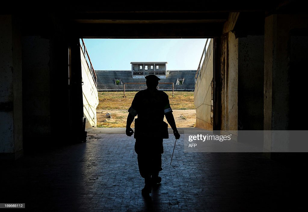 A handout photograph taken on January 12, 2013 and released on January 16 by the African Union-United Nations Information Support Team, shows a Ugandan soldier serving with the African Union Mission in Somalia (AMISOM) walking onto the former football pitch inside Mogadishu National Stadium. Formerly a main base for the Al-Qaeda-allied violent extremist group Al Shabaab, the once impressive stadium was used as a headquarters for the group's operations in Mogadishu, a training ground for their fighters and a site where they executed prisoners and tested and assembled improvised explosive devices (IEDs). After two decades of near-constant conflict, Somalia is enjoying its longest period of peace and growing security since the Al-Qaeda-allied violent extremist group Al Shabaab was driven from Mogadishu in August 2011. Under the Shabaab's draconian rule, social pastimes and sports such as football were banned but residents of the city and elsewhere across Somalia.