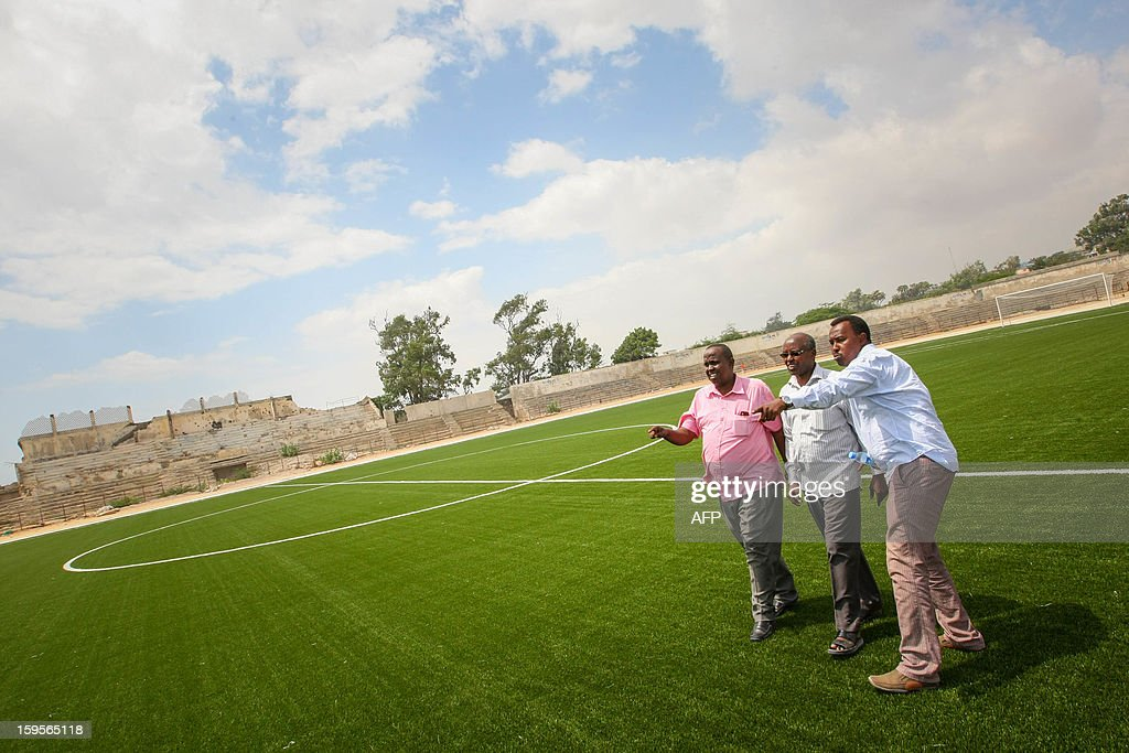 A handout photograph taken on January 12, 2013 and released on January 16 by the African Union-United Nations Information Support Team, shows members of the Somali Football Federation (SFF) walking across the football pitch inside Baanadir Stadium in the Abd-Aziz District of the Somali capital Mogadishu. The field that has recently been re-surfaced with a new artificial playing surface funded by FIFA, the SFF with repair work to begin on the seats, parking and facilities of the 7,500-capacity stadium. After two decades of near-constant conflict, Somalia is enjoying its longest period of peace and growing security since the Al-Qaeda-allied violent extremist group Al Shabaab was driven from Mogadishu in August 2011. Under the Shabaab's draconian rule, social pastimes and sports such as football were banned but residents of the city and elsewhere across Somalia.