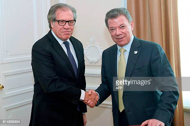 Handout picture released by the Colombian Presidency showing Colombian President Juan Manuel Santos shaking hands with the Secretary General of the...