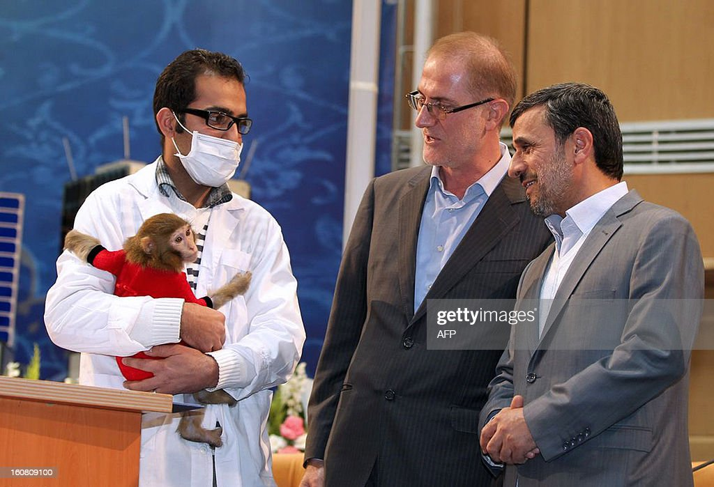 A handout picture released by the Iranian presidency website shows President Mahmoud Ahmadinejad looking at a space monkey during a ceremony to mark Iran's National Day of Space Technology in Tehran on February 4, 2013. Ahmadinejad unveiled two small satellites, 'Nahid' and 'Zohreh' (Venus in Farsi and Arabic) and said that he is ready 'to be the first man in space' sent by the Iranian scientists under the ambitious national programme which claims aiming to put a human being into orbit before 2020. AFP PHOTO/HO / IRANIAN PRESIDENCY WEBSITE/ARMAN TEIMUR +++ RESTRICTED TO EDITORIAL USE - MANDATORY CREDIT '