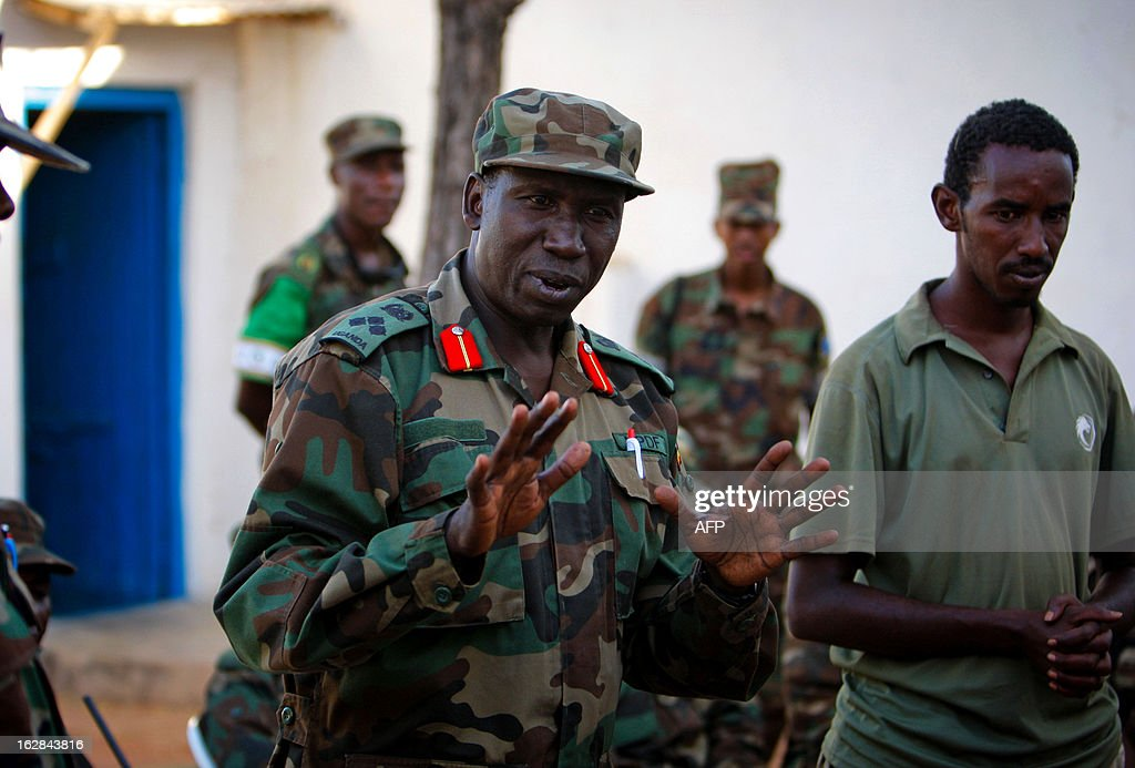 A handout picture taken and released by the African Union-United Nations Information Support team on February 28, 2013 shows Brigadier General Michael Ondoga, Contingent Commander for Ugandan troops serving with the African Union Mission in Somalia (AMISOM) speaking with elders during a meeting in the central Somali town of Buur-Hakba following it's capture the day before from the Al-Qaeda-affiliated extremist group Al Shabaab by the Somali National Army (SNA), supported by AMISOM forces. The strategically important town linking the capital Mogadishu and the hinterlands of central Somalia was liberated without a shot being fired, marking a significant loss for the group. Under the Shabaab's repressive and violent rule, social and leisure past-times such as football were banned in every form including watching and playing. The town, located 64kms east of Baidoa, Somalia's second city, was a stronghold of the Shabaab where they extorted high levies of illegal taxation on the local civilian populations and used it as a base from where they planned and launched attacks against government forces and installations, AMISOM and the Somali population. Buur-Hakba is the latest in a string of notable territorial losses for the extremist group to SNA and AMISOM forces over the last 18 months, which has seen their area of influence and control over towns and areas across Somalia steadily and rapidly decrease. AFP PHOTO / AU-UN IST PHOTO / STUART PRICE CREDIT 'AFP PHOTO / AU-UN IST PHOTO / STUART PRICE' - NO