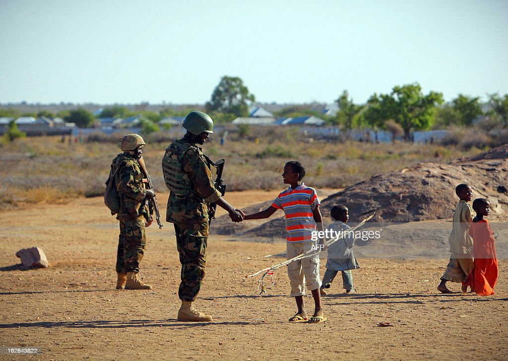 A handout picture taken and released by the African Union-United Nations Information Support team on February 28, 2013 shows a young Somali boy (C) greeting a Ugandan soldier serving with the African Union Mission in Somalia (AMISOM) in the central Somali town of Buur-Hakba following it's capture the day before from the Al-Qaeda-affiliated extremist group Al Shabaab by the Somali National Army (SNA), supported by AMISOM forces. The strategically important town linking the capital Mogadishu and the hinterlands of central Somalia was liberated without a shot being fired, marking a significant loss for the group. Under the Shabaab's repressive and violent rule, social and leisure past-times such as football were banned in every form including watching and playing. The town, located 64kms east of Baidoa, Somalia's second city, was a stronghold of the Shabaab where they extorted high levies of illegal taxation on the local civilian populations and used it as a base from where they planned and launched attacks against government forces and installations, AMISOM and the Somali population. Buur-Hakba is the latest in a string of notable territorial losses for the extremist group to SNA and AMISOM forces over the last 18 months, which has seen their area of influence and control over towns and areas across Somalia steadily and rapidly decrease. AFP PHOTO / AU-UN IST PHOTO / STUART PRICE CREDIT 'AFP PHOTO / AU-UN IST PHOTO / STUART PRICE' - NO