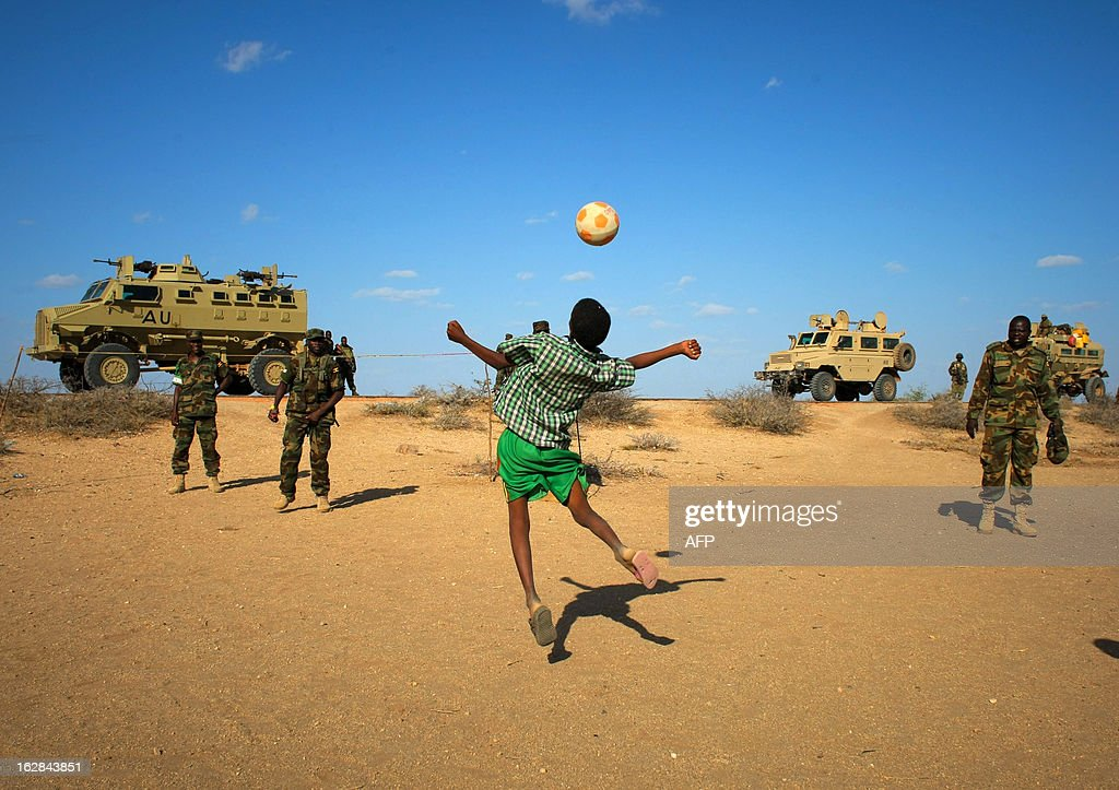 A handout picture taken and released by the African Union-United Nations Information Support team on February 28, 2013 shows Ugandan soldiers serving with the African Union Mission in Somalia (AMISOM) play football with young Somali boys in the central Somali town of Buur-Hakba following it's capture the day before from the Al-Qaeda-affiliated extremist group Al Shabaab by the Somali National Army (SNA), supported by AMISOM forces. The strategically important town linking the capital Mogadishu and the hinterlands of central Somalia was liberated without a shot being fired, marking a significant loss for the group. Under the Shabaab's repressive and violent rule, social and leisure past-times such as football were banned in every form including watching and playing. The town, located 64kms east of Baidoa, Somalia's second city, was a stronghold of the Shabaab where they extorted high levies of illegal taxation on the local civilian populations and used it as a base from where they planned and launched attacks against government forces and installations, AMISOM and the Somali population. Buur-Hakba is the latest in a string of notable territorial losses for the extremist group to SNA and AMISOM forces over the last 18 months, which has seen their area of influence and control over towns and areas across Somalia steadily and rapidly decrease. AFP PHOTO / AU-UN IST PHOTO / STUART PRICE CREDIT 'AFP PHOTO / AU-UN IST PHOTO / STUART PRICE' - NO