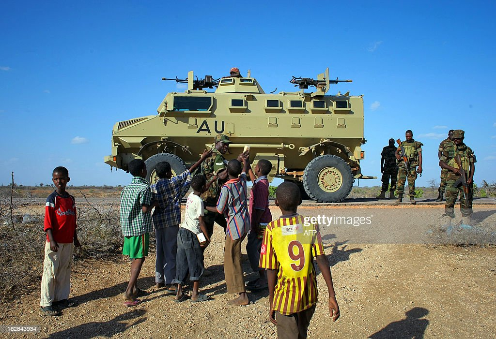 A handout picture taken and released by the African Union-United Nations Information Support team on February 28, 2013 shows a Ugandan soldier serving with the African Union Mission in Somalia (AMISOM) handing out biscuits to young Somali children in the central Somali town of Buur-Hakba following it's capture the day before from the Al-Qaeda-affiliated extremist group Al Shabaab by the Somali National Army (SNA), supported by AMISOM forces. The strategically important town linking the capital Mogadishu and the hinterlands of central Somalia was liberated without a shot being fired, marking a significant loss for the group. Under the Shabaab's repressive and violent rule, social and leisure past-times such as football were banned in every form including watching and playing. The town, located 64kms east of Baidoa, Somalia's second city, was a stronghold of the Shabaab where they extorted high levies of illegal taxation on the local civilian populations and used it as a base from where they planned and launched attacks against government forces and installations, AMISOM and the Somali population. Buur-Hakba is the latest in a string of notable territorial losses for the extremist group to SNA and AMISOM forces over the last 18 months, which has seen their area of influence and control over towns and areas across Somalia steadily and rapidly decrease. AFP PHOTO / AU-UN IST PHOTO / STUART PRICE CREDIT 'AFP PHOTO / AU-UN IST PHOTO / STUART PRICE' - NO