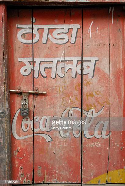 A handpainted CocaCola sign in both Hindi and English decorates a closed shop door
