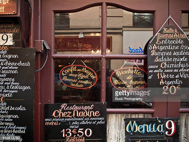Hand-painted menus hanging on the door of an old-fashioned restaurant in the center of Paris