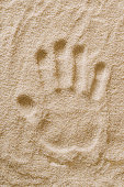 Handprint in the sand. Handmark and imprint of the left hand of an adult in dry ocherous sand. Macro photo close up from above.