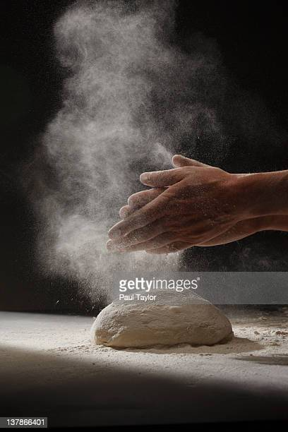 Hands and Cloud of Flour Over Dough