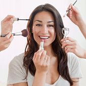 Hands applying makeup to Hispanic woman's face