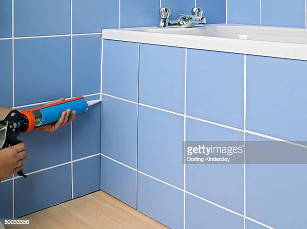 Hands applying sealant to side of bath