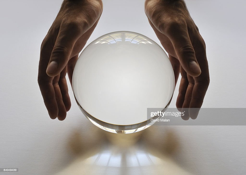 Hands around a crystal ball : Stock Photo