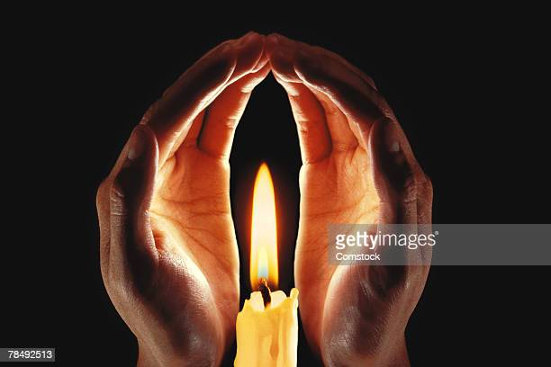 Hands around lit candle