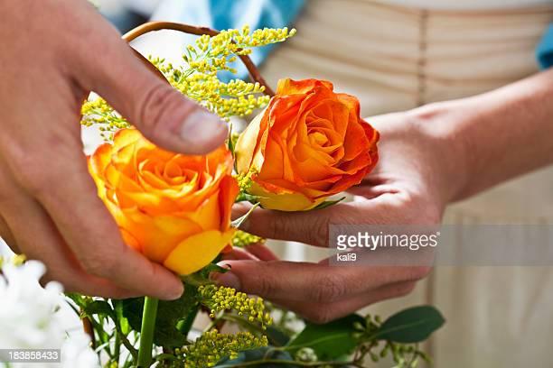 Hands arranging fresh cut flowers in vase