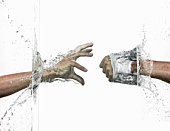 Hands breaking a  water wall