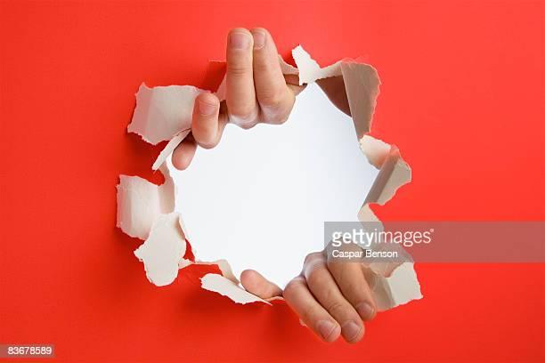 Hands breaking through a wall