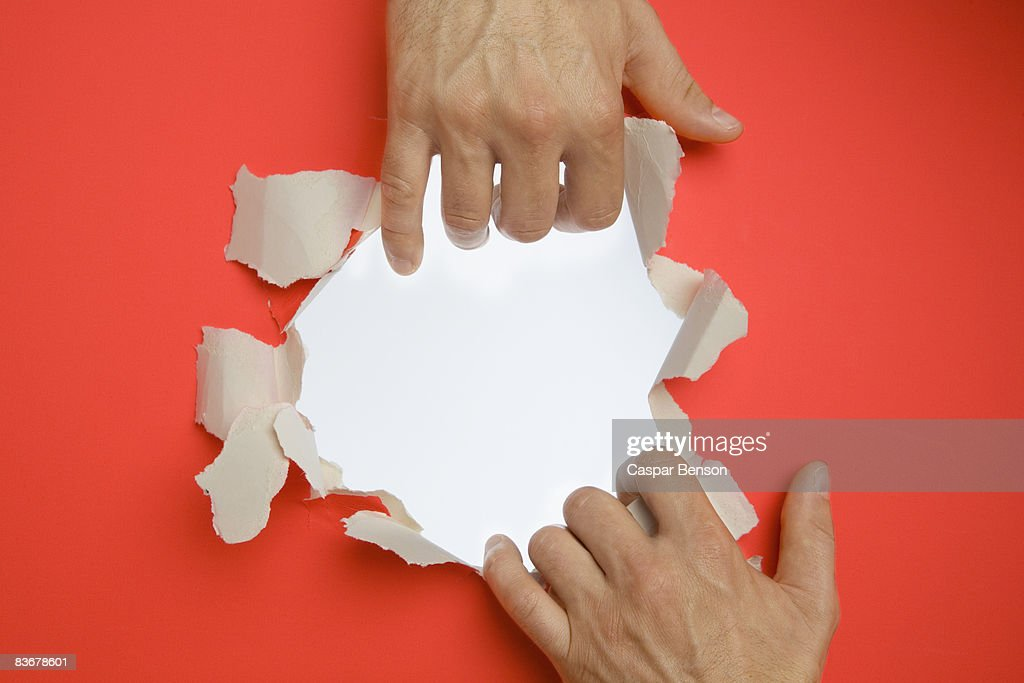 Hands breaking through a wall