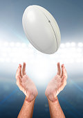 A pair of male hands reaching upwards to catch a rugby ball on a floodlit stadium background - 3D render