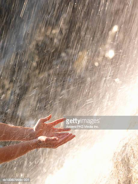 Hands catching water falling from waterfall