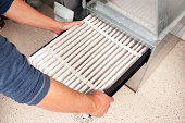 Male hands are installing a furnace air filter. This filter is not brand new but it is relatively clean, it was removed for inspection. This would be a typical filter style found in a high end newer h