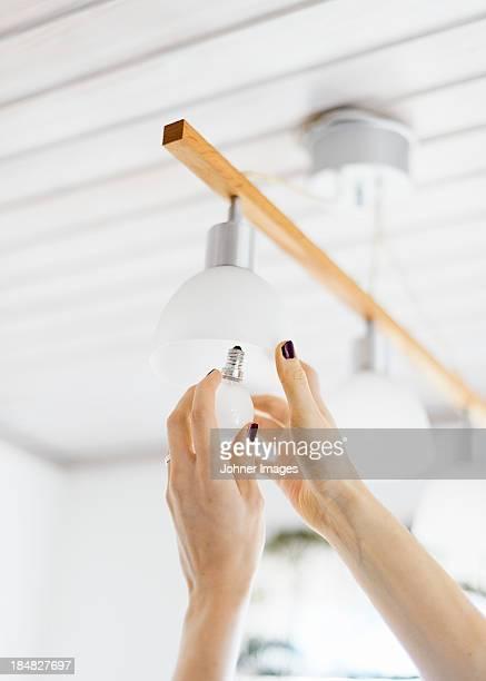 Hands changing light bulb