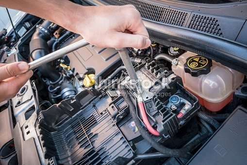 Hands Checking A Car Battery Bolt With Wrench Stock Photo