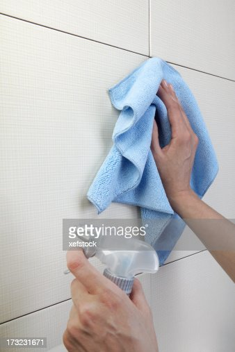 Hands cleaving a white surface with a cloth and spray