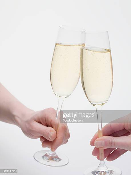 Hands clinking glasses of sparkling wine, close-up