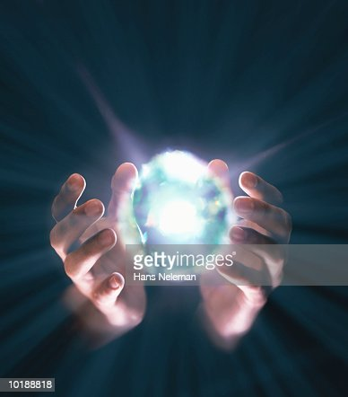 Hands coming around bright ball of light