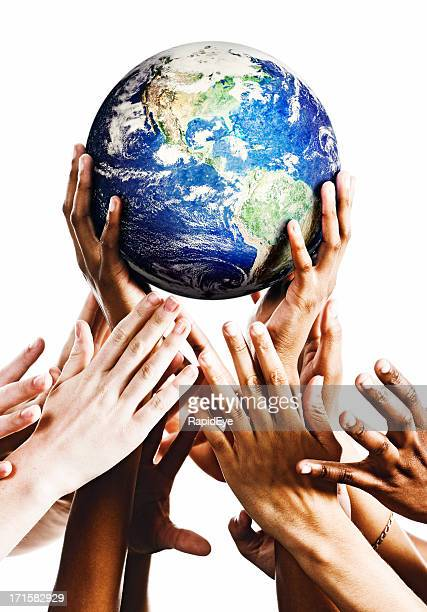 Hands cradling Planet Earth as others try to snatch it