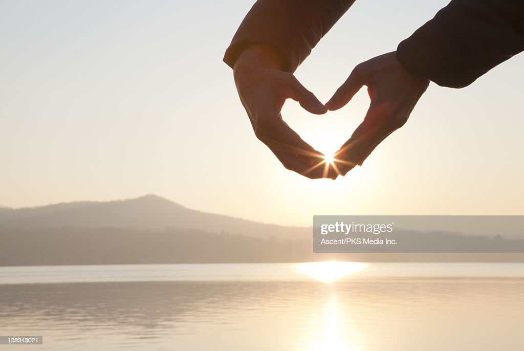 Hands create 'heart' shape over lake, sunrise : Stock Photo