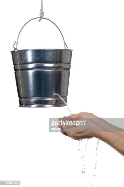 Hands cupped under a silver bucket leaking water