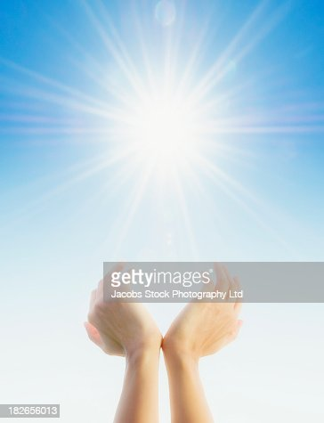 Hands cupping around sun in blue sky