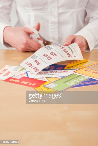 Hands cutting out savings coupons.