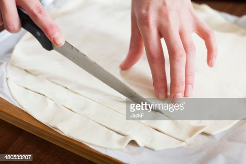 hands cutting store-bought dough : Stock Photo