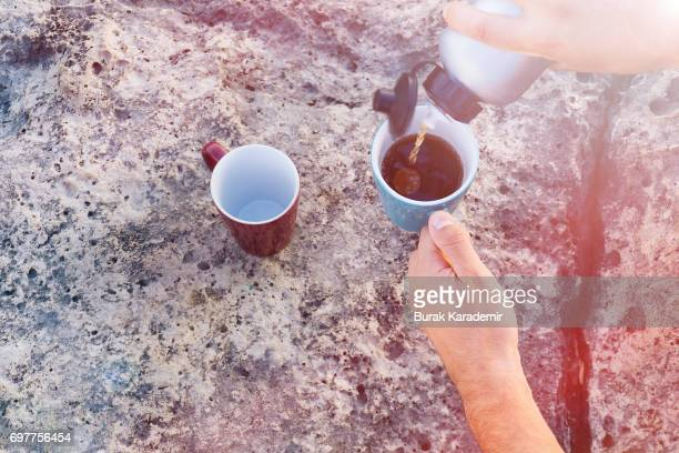 Hands filling the cups Thermos and cups