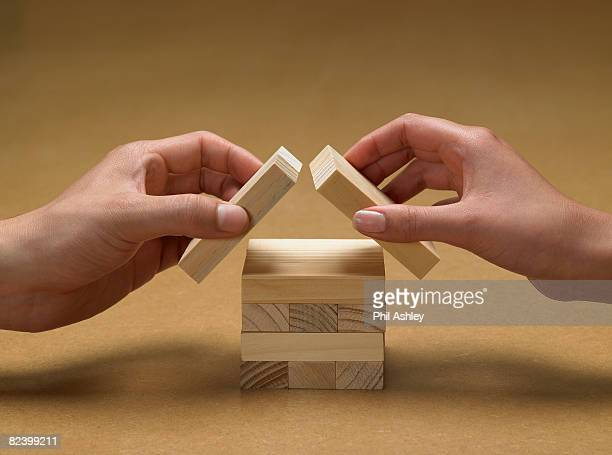 hands forming a house from wooden blocks