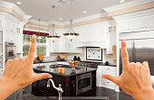 Female Hands Framing A Beautiful Custom Kitchen Interior.